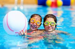Amigos adolescentes que juegan con la bola en la piscina Fotos de archivo libres de regalías