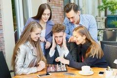 Amigos adolescentes que juegan a un juego de ajedrez y que piensan en un fondo del café Concepto del juego del ajedrez Imagen de archivo