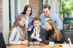 Amigos adolescentes que juegan a un juego de ajedrez y que piensan en un fondo del café Concepto del juego del ajedrez Imagenes de archivo