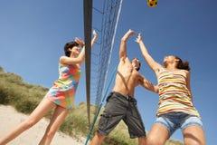 Amigos adolescentes que juegan a voleibol en la playa Imagen de archivo libre de regalías