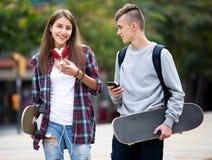 Amigos adolescentes que levam skates na cidade Fotos de Stock Royalty Free