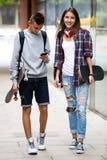 Amigos adolescentes que llevan los monopatines en la ciudad Imágenes de archivo libres de regalías