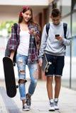 Amigos adolescentes que llevan los monopatines en la ciudad Fotos de archivo