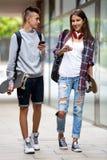 Amigos adolescentes que llevan los monopatines en la ciudad Foto de archivo libre de regalías