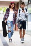Amigos adolescentes que llevan los monopatines en la ciudad Imagenes de archivo