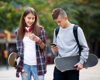 Amigos adolescentes que llevan los monopatines en la ciudad Fotos de archivo libres de regalías