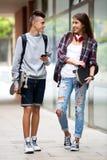 Amigos adolescentes que llevan los monopatines en la ciudad Foto de archivo