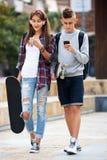 Amigos adolescentes que llevan los monopatines en la ciudad Imagen de archivo