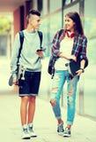 Amigos adolescentes que llevan los monopatines en la ciudad Fotografía de archivo libre de regalías