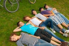 Amigos adolescentes que mienten en la hierba Fotografía de archivo libre de regalías