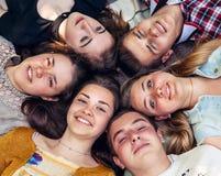 Amigos adolescentes que mienten junto en círculo Fotos de archivo