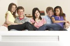 Amigos adolescentes que miran la televisión en el país Imagen de archivo
