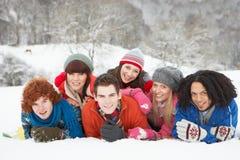 Amigos adolescentes que se divierten en el paisaje Nevado Imagen de archivo libre de regalías