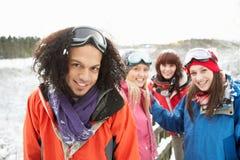 Amigos adolescentes que se divierten en el paisaje Nevado Foto de archivo libre de regalías