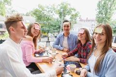 Amigos adolescentes que se divierten que juega con las etiquetas engomadas en las frentes en un fondo del café Concepto de la act Fotografía de archivo