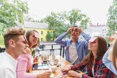 Amigos adolescentes que se divierten que juega con las etiquetas engomadas en las frentes en un fondo del café Concepto de la act Fotografía de archivo libre de regalías