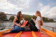 Amigos adolescentes que se relajan en el barco del pedal Imagenes de archivo