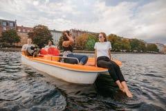 Amigos adolescentes que se relajan en el barco del pedal en el lago Fotos de archivo
