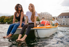Amigos adolescentes que se relajan en el barco del pedal en el lago Fotografía de archivo