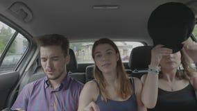 Amigos adolescentes que se sientan en asiento de pasajero dentro del coche del uber del taxi que disfruta del paseo a través de l almacen de video