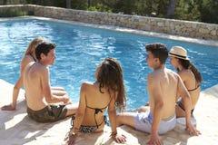 Amigos adolescentes que se sientan en el borde de una piscina, visión trasera Foto de archivo libre de regalías
