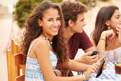 Amigos adolescentes que se sientan en el ½ del ¿de Cafï usando los dispositivos de Digitaces Imagenes de archivo