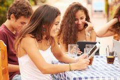 Amigos adolescentes que se sientan en el ½ del ¿de Cafï usando los dispositivos de Digitaces Imagen de archivo