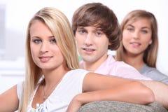 Amigos adolescentes que se sientan en el sofá Imágenes de archivo libres de regalías