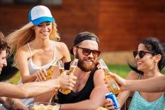 Amigos adolescentes que se sientan en la tabla y que se divierten al aire libre Fotografía de archivo