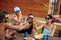 Amigos adolescentes que se sientan en la tabla y que se divierten al aire libre Foto de archivo libre de regalías