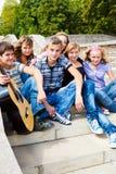 Amigos adolescentes que se sientan en las escaleras Imagenes de archivo