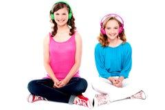 Amigos adolescentes que se sientan en música que escucha del suelo Fotos de archivo