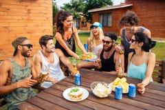 Amigos adolescentes que tienen partido de la comida campestre al aire libre Fotografía de archivo