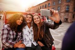 Amigos adolescentes que toman el selfie en el triciclo Fotos de archivo