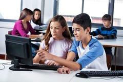 Amigos adolescentes que usan el ordenador en laboratorio fotografía de archivo