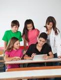 Amigos adolescentes que usan la tableta de Digitaces en el escritorio Fotografía de archivo