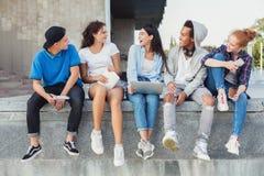 Amigos adolescentes que usan los artilugios y hablando el uno al otro en la vida real imágenes de archivo libres de regalías