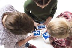 Amigos adolescentes que usan smartphones con el logotipo del facebook aislado en blanco Imagen de archivo