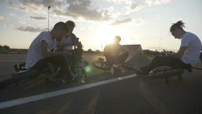 Amigos adolescentes relajados de los motoristas que toman una rotura después de un entrenamiento biking en el circuito usando los metrajes