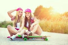 Amigos adolescentes sonrientes del inconformista con el monopatín, imagen colorised con el sunflare Imagen de archivo libre de regalías