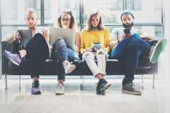 Amigos adultos de los inconformistas del grupo que sientan a Sofa Using Modern Gadgets Concepto del trabajo en equipo de la amist foto de archivo