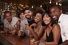 Amigos adultos jovenes por la barra en un partido que mira a la cámara Fotos de archivo