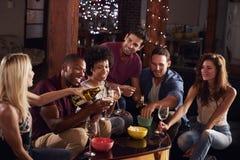 Amigos adultos jovenes que beben y que comen los bocados en casa Imagen de archivo libre de regalías