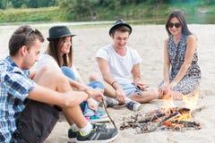 Amigos adultos jovenes que cuelgan alrededor en la hoguera en Sandy Beach Imagenes de archivo