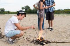 Amigos adultos jovenes que cuelgan alrededor en la hoguera en Sandy Beach Imagen de archivo libre de regalías