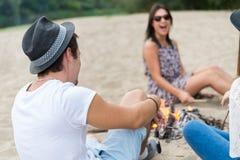 Amigos adultos jovenes que cuelgan alrededor en la hoguera en Sandy Beach Fotografía de archivo