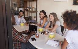 Amigos adultos jovenes que cuelgan hacia fuera en el café, a través vista ventana Foto de archivo