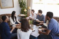 Amigos adultos jovenes que hablan alrededor de una tabla en una cafetería imagen de archivo