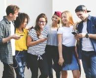 Amigos adultos jovenes que usan concepto de la cultura joven de los smartphones junto al aire libre Fotos de archivo libres de regalías