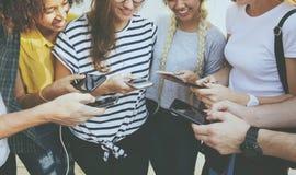 Amigos adultos jovenes que usan concepto de la cultura joven de los smartphones junto al aire libre Imagen de archivo